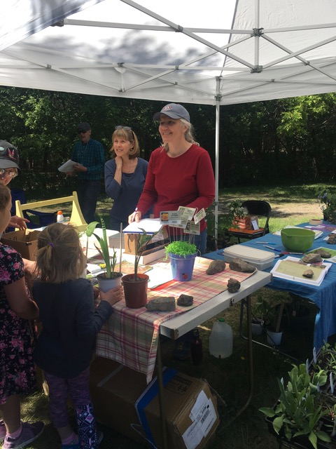 Two people assisting buyers with their native plants.