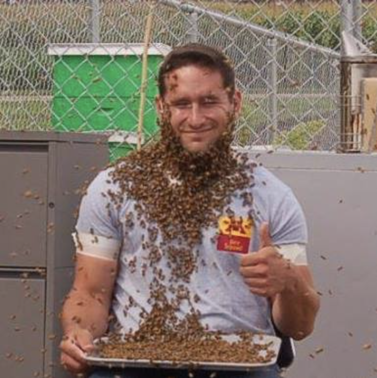 man with honeybees on his face and torso